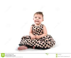baby sitting on the floor in a beautiful dress stock photo