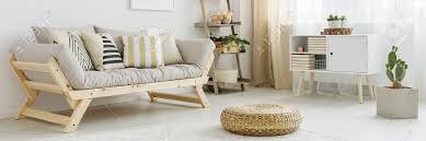 holzsofa mit kissen im weißen wohnzimmer mit leiterregal