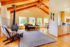 wohnzimmer mit hohen gewölbe celing mit balken zimmer mit antiken herd sofa und sessel ansicht der küchenbereich eingerichtet