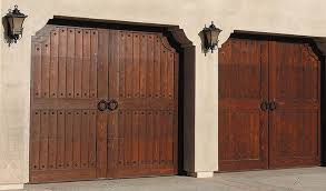 Two Wooden Carriage House Garage Doors Are Outlined With Decorative Wrought Iron Embellishments And Have