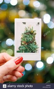 Woman Holding An Instant Print Of A Christmas Tree In Front The