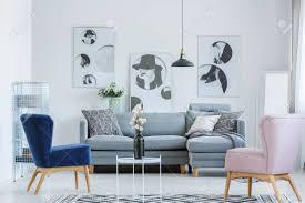 rosa und blaue lehnsessel im gemütlichen wohnzimmer mit grauem sofa und schwarzer vase auf kleinem kaffeetisch