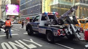 100 New Tow Trucks NYPD TOW TRUCK TOWING A CAR ON 8TH AVENUE IN THE HELLS KITCHEN AREA
