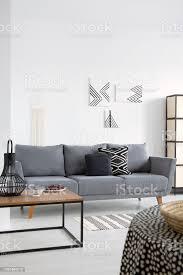laterne auf tisch in der nähe grauen sofa in weiß wohnzimmer interieur mit plakaten an der wand echtes foto stockfoto und mehr bilder design