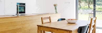 esszimmer mit offener küche mit holztisch stühle breite tischplatte und terrassen eintrag