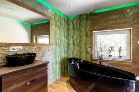 luxuriöse badezimmer mit holz und stein effekt fliesen schwarz badewanne und aufsatzbecken