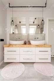 zwei waschbecken weißer schrank und wandspiegel in einem geräumigen modernen badezimmer
