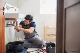 foto auf lager klempner arbeitet daran undichtes waschbecken im badezimmer zu reparieren