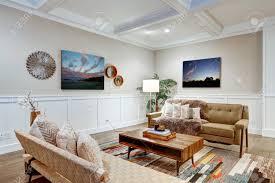 lovely handwerker stil wohnzimmer mit kassettendecke über hellbeige wände mit brett und latten holzvertäfelung bequemes sofa mit kissen und taupe
