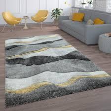wohnzimmer teppich kurzflor mit wellen muster in anthrazit grau und gold