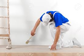Painter Man At Work With Brush Painting A White Wall Stock Photo