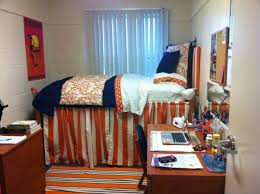 Simple College Dorm Room Idea With White Bedding And Orange Stripe Patterned Sleeve Wooden Desk