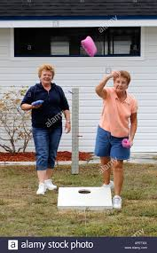 Female Senior Retired Citizens Play Game Of Bean Bag Toss In A Recreational Vechile Camping Park Bonita Springs Florida