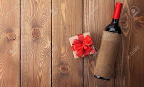 Red Wine Bottle And Valentines Day Gift Box Over Rustic Wooden Table Background With Copy