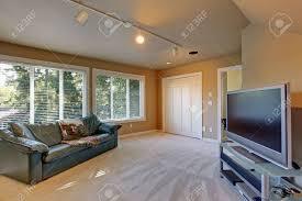 wohnzimmer innenraum in beige farbe mit weichen teppichboden mit grünen ledercouch und tv