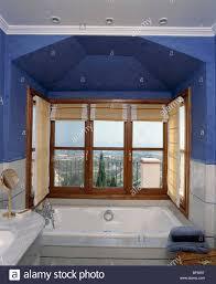 große badewanne vor fenster im blauen spanischen badezimmer