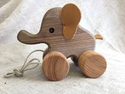 pull along toy elephant a joyfully looking wooden animal on