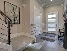 heller eingangsbereich mit cremefarbenen wänden die moderne glastüren über grauen holzböden hervorheben beinhaltet einen einbauschrank mit weißen
