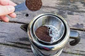 Coffee Grounds Being Poured Into A Percolator Coffeemaker