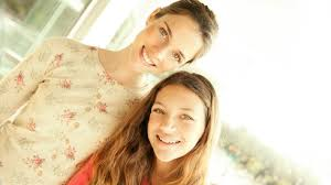 A Mom And Daughter Smiling At The Camera In Kitchen