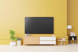 schrank tv und gelbe wand im wohnzimmer premium foto