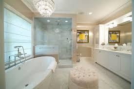 bathtub under chandelier transitional bathroom blue water
