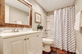 weiß töne badezimmer mit waschbeckenunterschrank und holzrahmen spiegel dekoriert mit bild blumentopf und gestreifter vorhang northwest usa