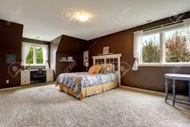 geräumige master schlafzimmer interieur mit weichen teppichboden und dunkelbraunen wände das zimmer verfügt über kleine büroecke am fenster