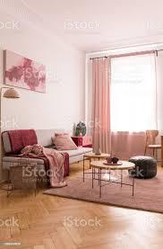 couchtische und oldschoolhocker auf pastell rosa teppich in eleganten wohnzimmer mit kissen und decken auf grauen bequemen stockfoto und mehr