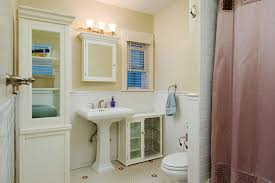 cottage bathroom with wainscoting built in bookshelf in san
