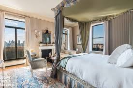 The Bedroom Features A Large Bed Along With Seats And Fireplace