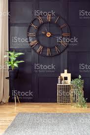 uhr auf schwarze wand im wohnzimmer interieur mit pflanzen und gold tischen in der nähe grauen teppich echtes foto stockfoto und mehr bilder