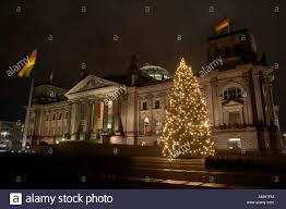 Christmas Tree And German Flag Flying Fluttering On Flagpole Outside Reichstag Building Berlin Germany