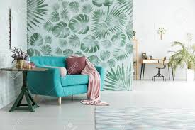blaue mit rosa kissen und tabelle im geräumigen wohnzimmer mit grüner tapete und arbeitsplatz