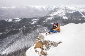 Couple Sitting On Edge Of Cliff In Mountains With Beautiful View Winter And Snow Stock