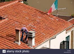 italy tuscany cortona repairing clay tile roof italian flag