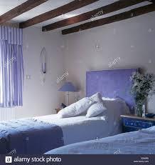 gepolsterte blaue kopfteil auf bett mit weißem leinen im