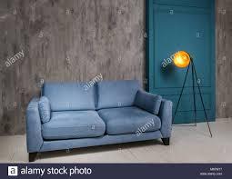 wohnzimmer einrichtung in dunklen farben mit blauen sofa und