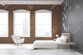 seitenansicht schlafzimmer in new york mit großen uhr auf graue wand ein riesiges bett und weißen sessel konzept der gemütlichen zimmer