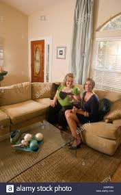 zwei frauen sitzen mit weingläsern auf sofa im wohnzimmer