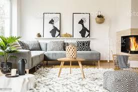 gemusterte hocker neben holztisch im afrikanischen wohnzimmer interieur mit plakaten echtes foto stockfoto und mehr bilder afrikanische kultur