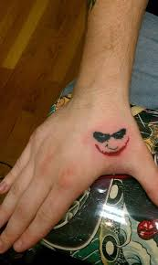 Funny Jokers Eyes And Smile Colored Hand Tattoo