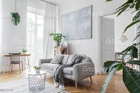 stilvolles skandinavisches wohnzimmer mit designmöbeln pflanzen bambusbuchständer und holztisch braunes holzparkett abstrakte malerei an der weißen