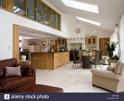 Limestone Flooring And Comfortable Armchairs In Large Modern Kitchen Dining Room Extension