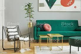 luxus und moderne wohngebäude mit grünem samt design sofa sessel tische und hocker tropische pflanze aus metall stehen graue wände mit abstrakter