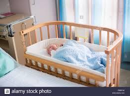 Newborn baby boy in bed New born child sleeping under a blue