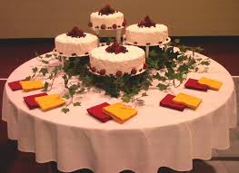 Elegant Wedding Cake Table Decoration Matched With Red Yellow Napkins And Batural Green Wine Leaves