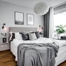 schlafzimmer in grau weiß mit kuschligen decken und bildern