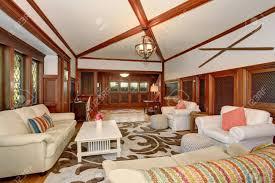 luxus wohnzimmer interieur mit braunen holz drum und dran gewölbte decke und balken weiße sofagarnitur und sessel mit rosa kissen schaffen