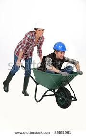 Two female construction workers racing in a wheelbarrow